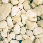 Beach stones surface. Marine mineral beauty harmony. White sea pebble cobblestones texture.