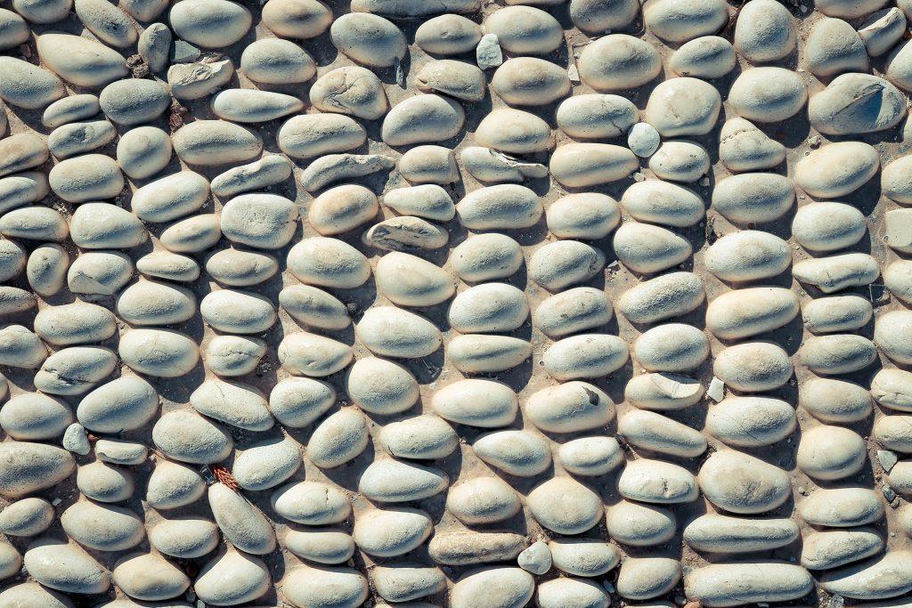 Stones pattern background. Lot of white masonry cladding pebble texture.