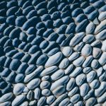 Lot of white masonry cladding pebble texture. Stones pattern background.