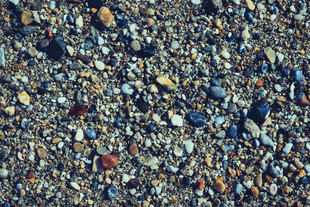 Lot of wet small stones on the beach with little pebbles texture. Nautical marine background.