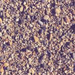 Lot of small stones on the beach with little pebbles texture. Nautical marine background.