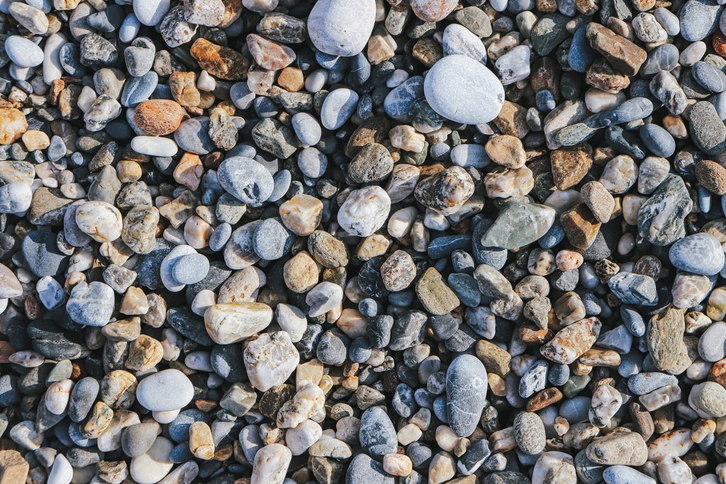 Pebble cobblestones on the beach. Nautical marine background.