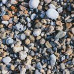 Pebble cobblestones on the beach. Nautical marine background.