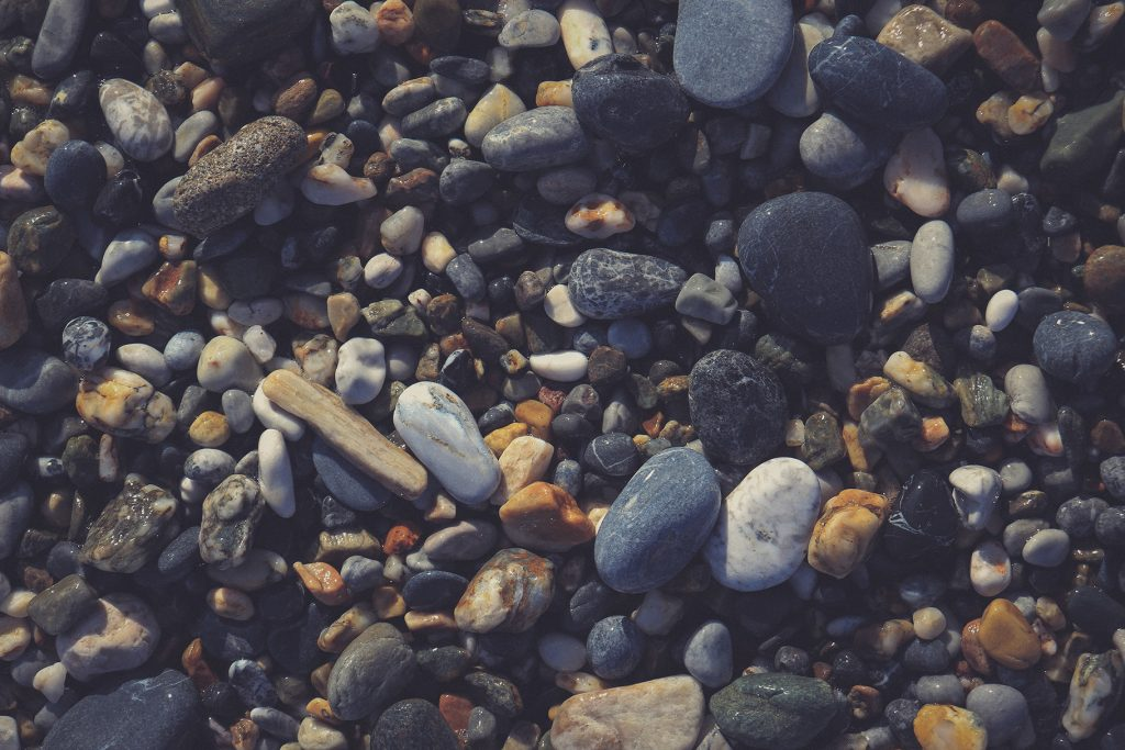Nautical marine background. Pebble cobblestones on the beach.