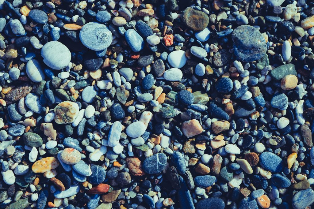 Nautical marine background. Pebble cobblestones on the beach.