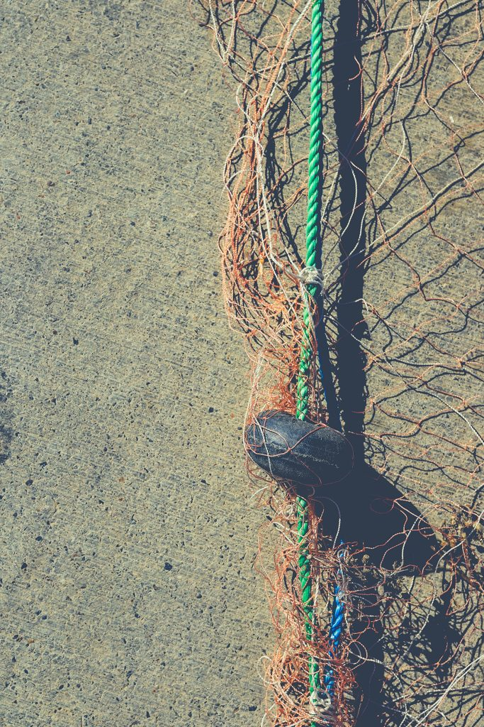 Fishnet with buoy on rope. Nautical marine background.