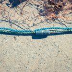 Fishnet with sinker on rope. Nautical marine background.