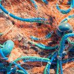 Crumpled fishnet with buoys on rope. Nautical marine background.