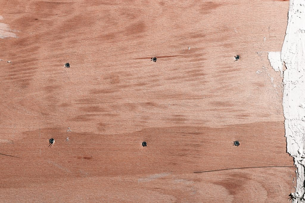 Wooded shipboard repairing texture. Plywood ship board with nails and screws background.