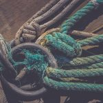 Lots of rope knots leading to moored boats. Iron mooring rings. Concrete pier surface. Nautical marine background.