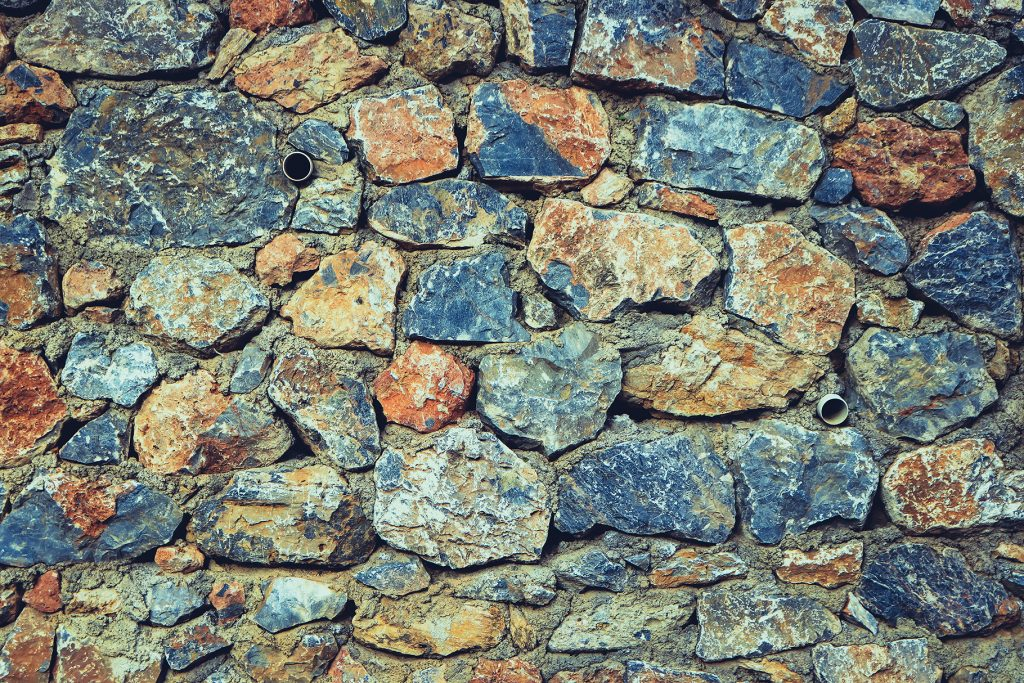 Rough stone background. Rocky masonry cobblestones cladding wall texture.