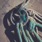 Concrete pier surface. Iron mooring rings. Lots of rope knots leading to moored boats. Nautical marine background.