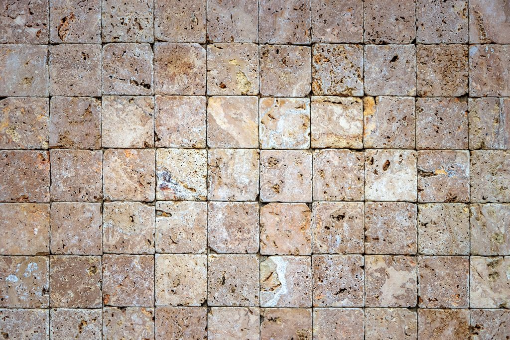 Travertine masonry tiles cladding wall texture. Square stones surface background.