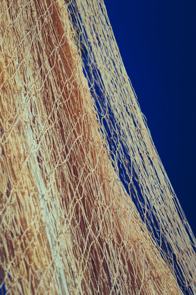 Nylon fishnet texture on the clear sky. Nautical marine background. Macro closeup.