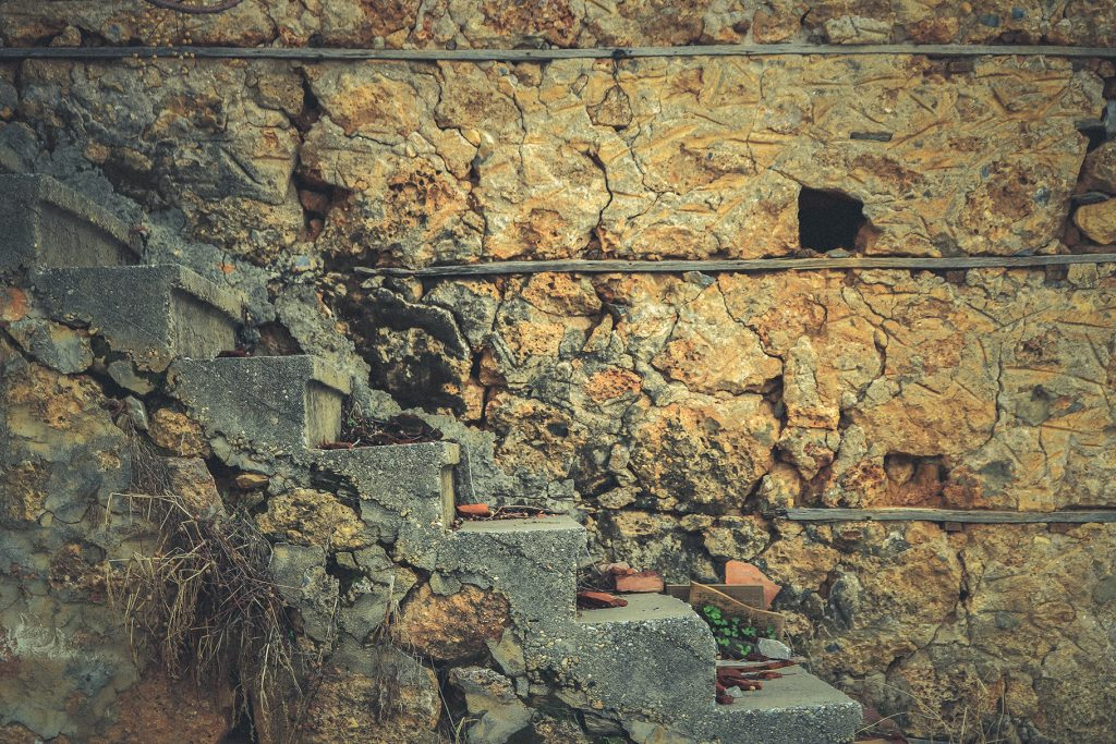 House of shell rock masonry cobblestones layers wall with stairs texture. Coquina surface background.