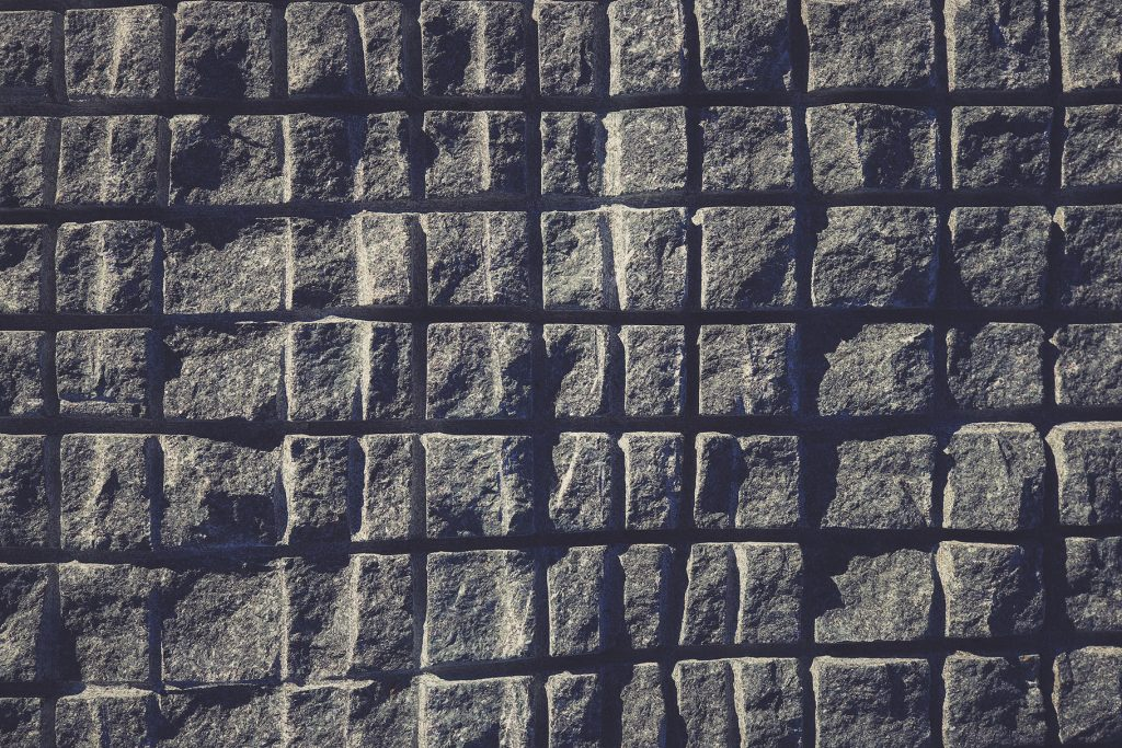 Sawn in a squares blue granite wall texture. Granite surface background.