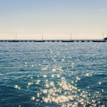 Long pier in the sea with sunshine reflection landscape.