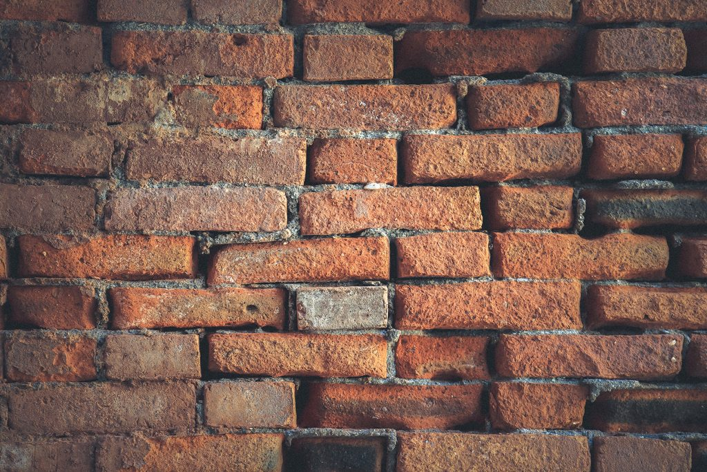 Weathered red bricks wall texture. Building stone surface background.