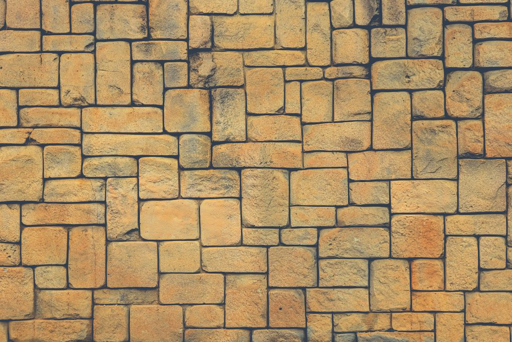 Masonry stone cladding wall texture. Geometric shapes surface background.