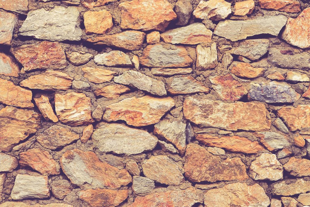 Rocky masonry cobblestones cladding wall texture. Rough stone background