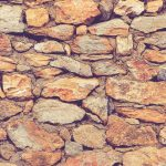 Rocky masonry cobblestones cladding wall texture. Rough stone background