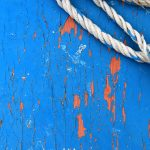 Blue painted wood texture with rope. Weathered paint wooden board. Natural wood structure background.