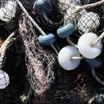Mixed up fishnet with rope and lot of buoys texture. Nautical marina background.